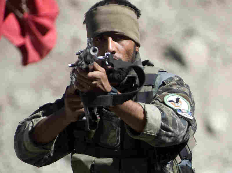 An Afghan special commando aims his weapon at journalists Wednesday