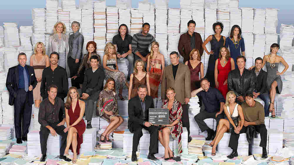 The cast of Guiding Light posed with thousands of scripts for their 15,000 episode press photo.