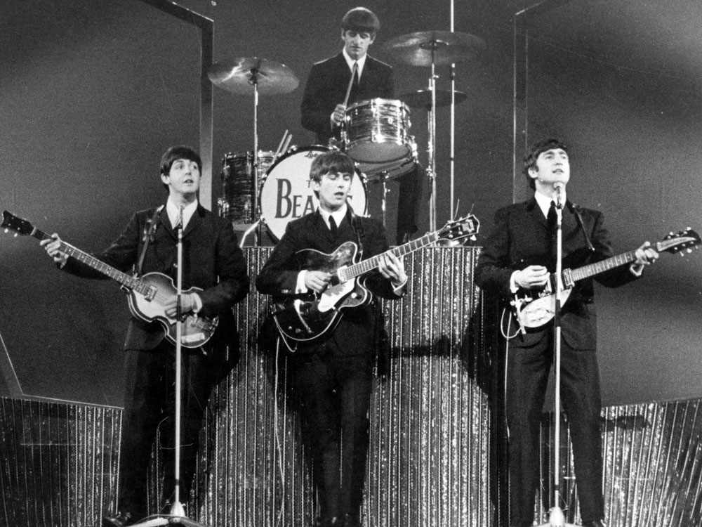 The Beatles perform at the London Palladium in 1963, the year that their first album, <em>Please Please Me,</em> was released in the UK.