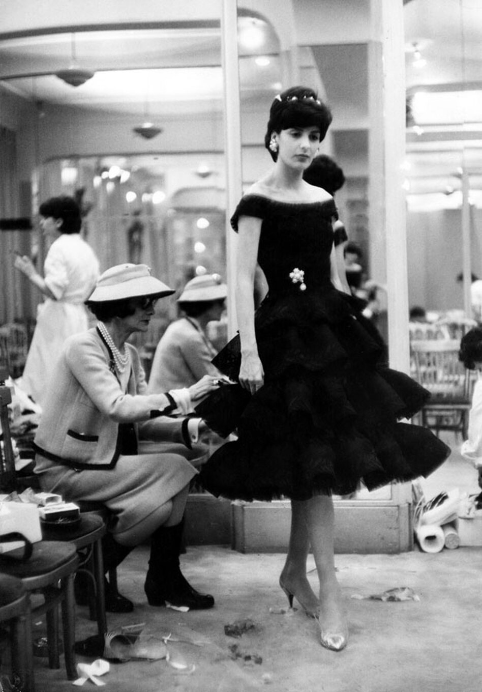 Chanel puts the finishing touches on one of her new designs in 1959.