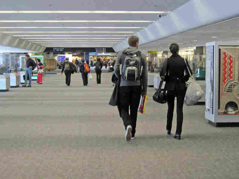 Travelers walk through the For Amusement Only exhibit in SFO's Terminal 3.