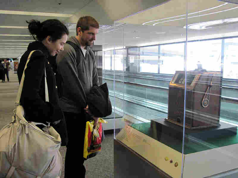 Lucy Verity and Luke Mirinovich pause in Terminal 3 to look at an old slot machine.
