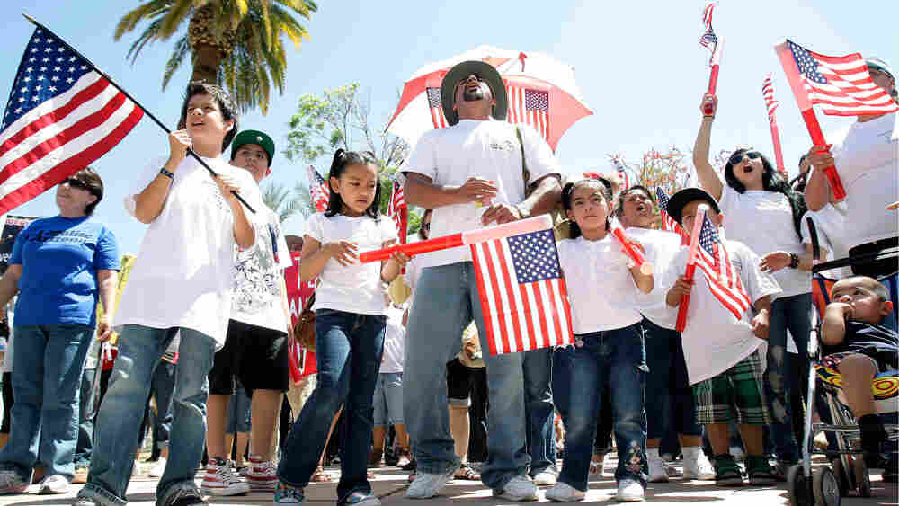 Protesters hold U.S. flags while rallying against Arizona's new immigration law