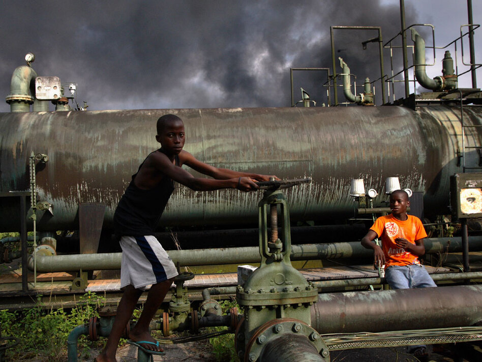 "Children play on a Nigerian oil-flow station in 2007. Nigeria, a major oil source for the United States, is riddled with ancient pipes and constant spills. That, plus the geopolitical challenges involved, is why much of Nigeria's crude is the kind of ""tough oil"" that author Michael Klare describes. (George Osodi/AP)"