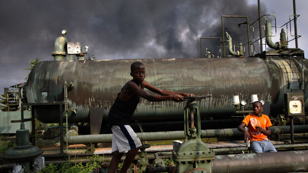 """Children play on a Nigerian oil-flow station in 2007. Nigeria, a major oil source for the United States, is riddled with ancient pipes and constant spills. That, plus the geopolitical challenges involved, is why much of Nigeria's crude is the kind of """"tough oil"""" that author Michael Klare describes. (AP)"""