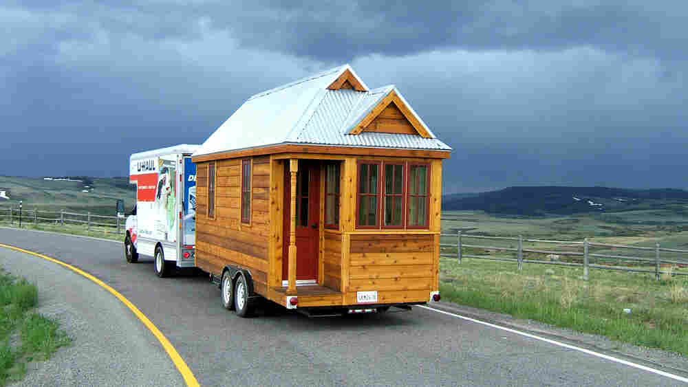 """The 130-square-foot """"Fencl"""" tiny house being pulled by a small truck."""