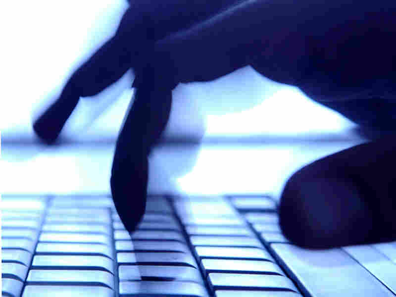 Shadowy fingers typing on keyboard