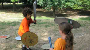 Jai Chablat-Yates and Georgia Silverman duel with foam swords at Brownstone Books' Camp Half-Blood.
