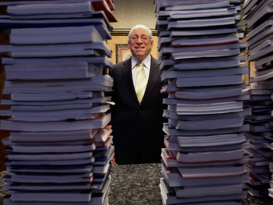 "Lawyer Peter Ticktin of the Ticktin Law Group in South Florida poses behind stacks of  depositions from ""robo-signers"" of foreclosure documents."