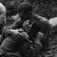 Soldiers hugging on battlefield