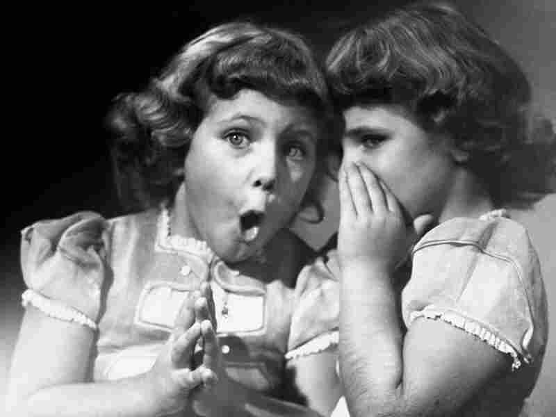 Sisters share a secret, circa 1950.