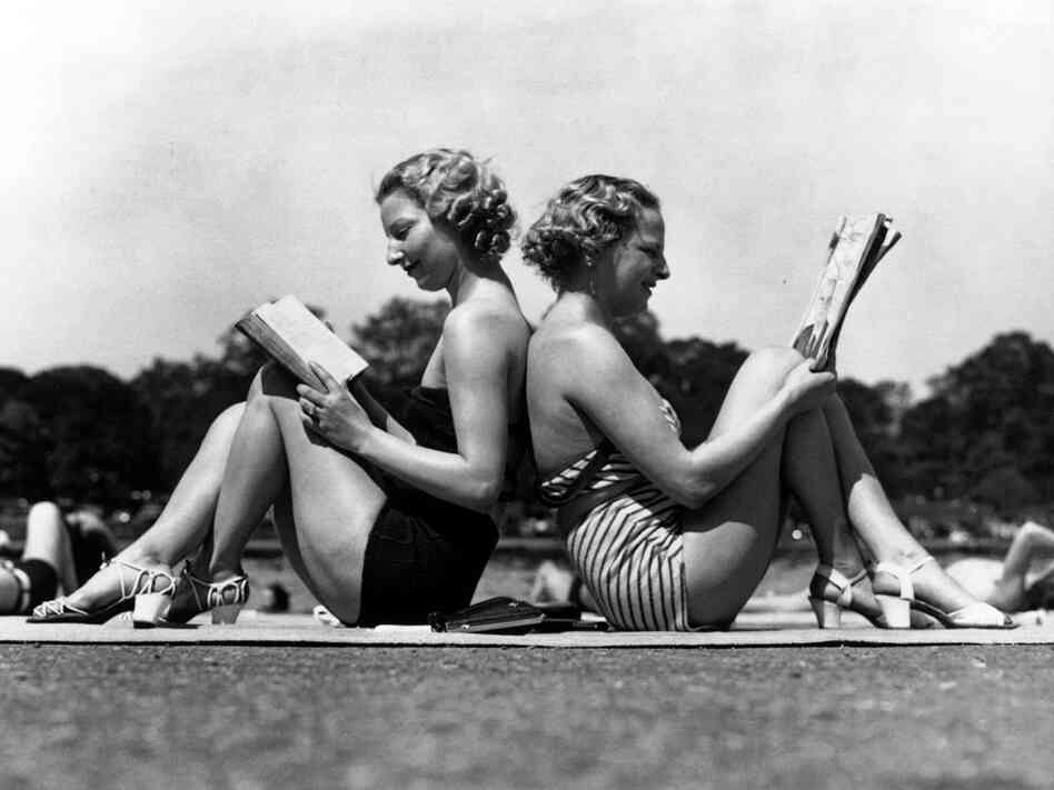 Two women reading back to back as they sunbathe in Hyde Park, London in May 1937.