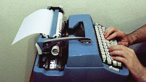 Man types on a typewriter