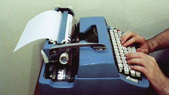 Man types on a typewriter