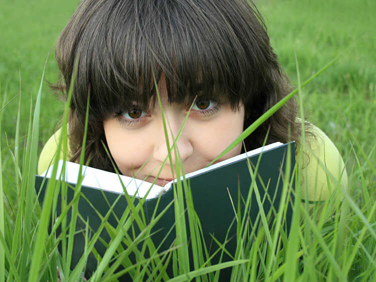 Teen reads book in the grass
