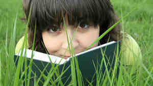 W: Teen reads book in the grass.