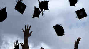 Graduates throw their caps into the air
