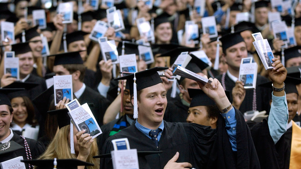 Notre Dame students hold up copies of 'To Kill A Mockingbird' during commencement ceremonies.