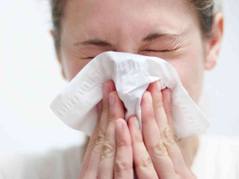 A woman sneezing into a tissue