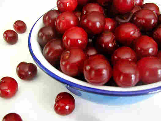 A blue-rimmed bowl overflowing with deep red sour cherries