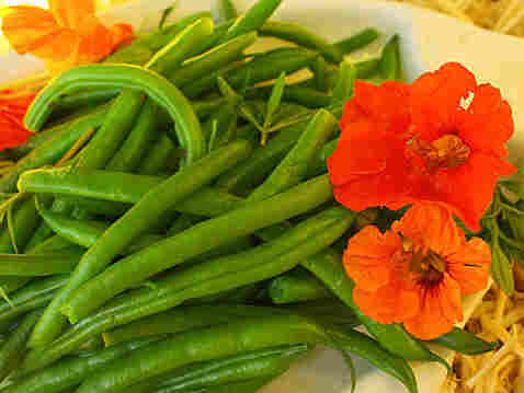 A pile of green beans on a platter with nasturtium flowers