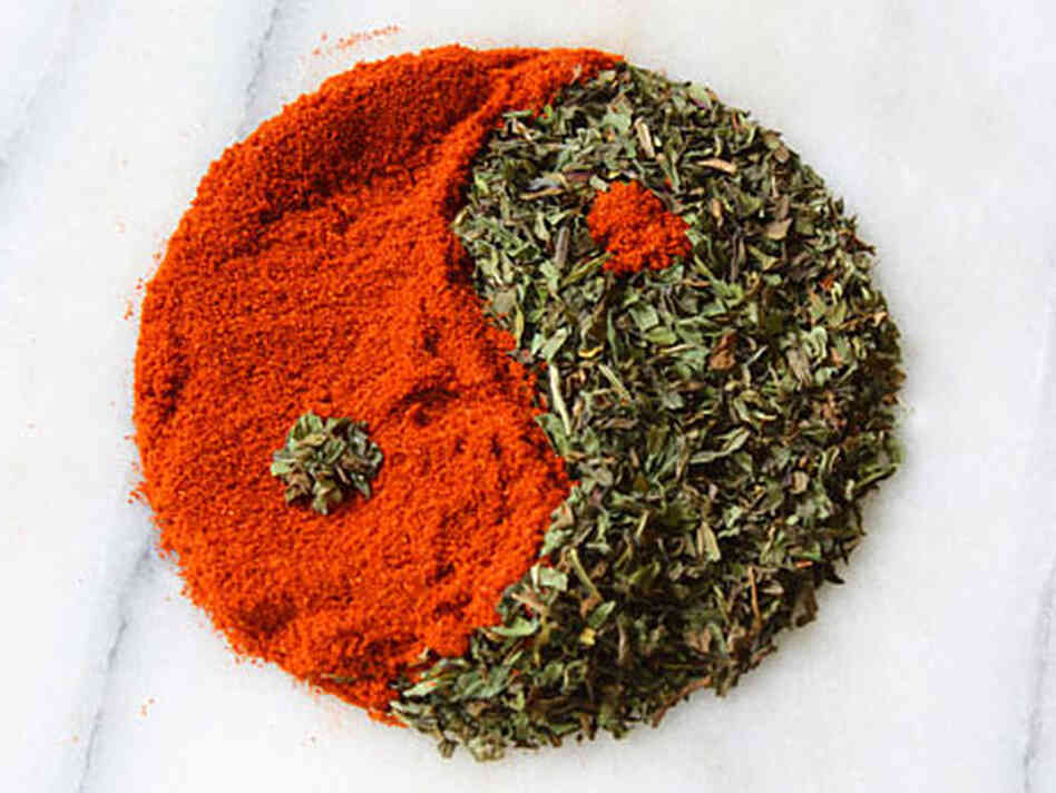 A yin and yang of red powdered paprika and green flaky dried mint