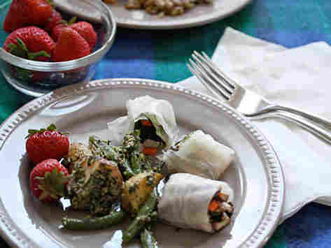 A picnic meal featuring fresh spring rolls, roasted potato-pesto salad and strawberries