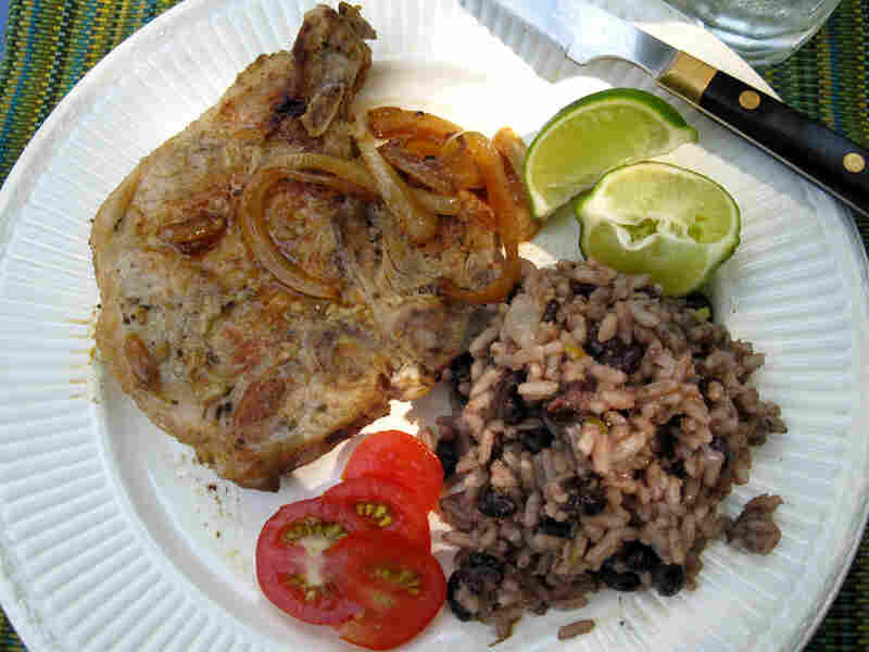 Cuban pork chops with a side of beans and rice, garnished with fresh tomato and lime wedges