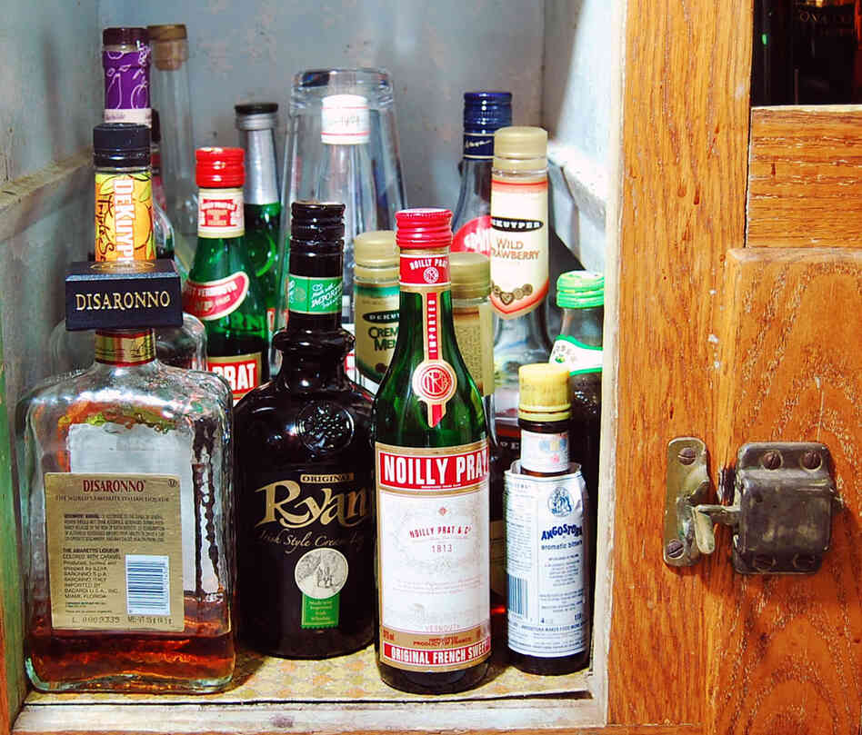 Assorted liquor bottles in a wood cabinet