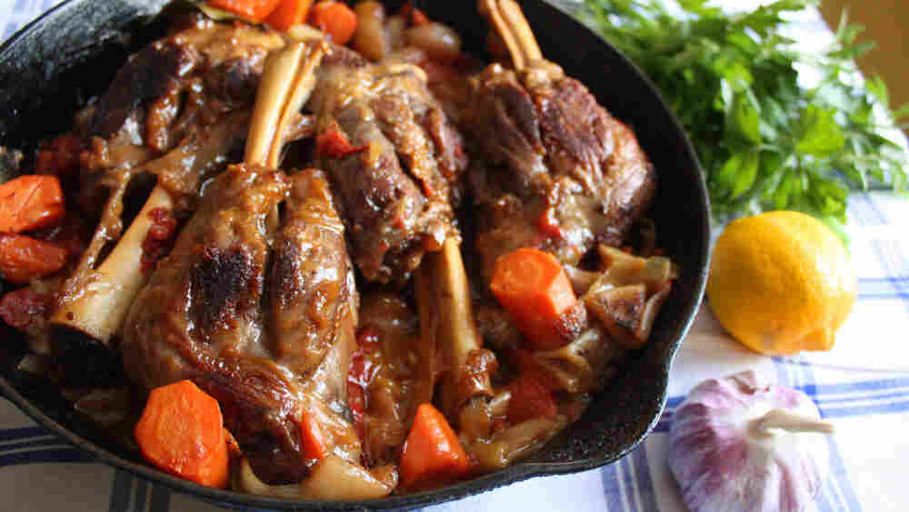 Lamb shanks and vegetables in a cast-iron pan, with parsley, lemon and garlic on a table