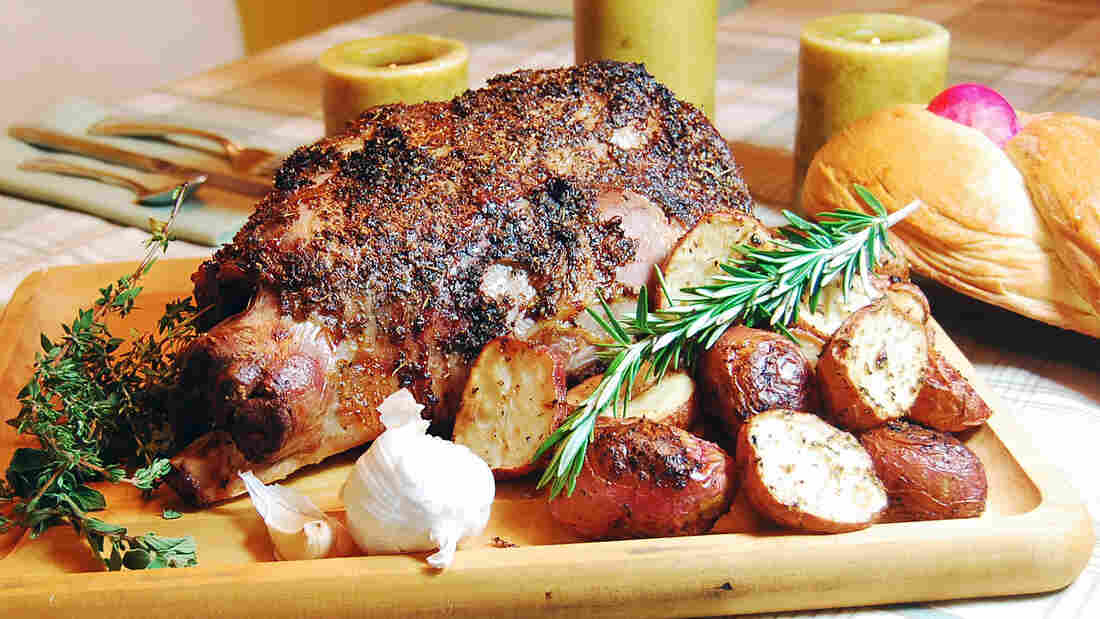 Roast leg of lamb on a wood cutting board