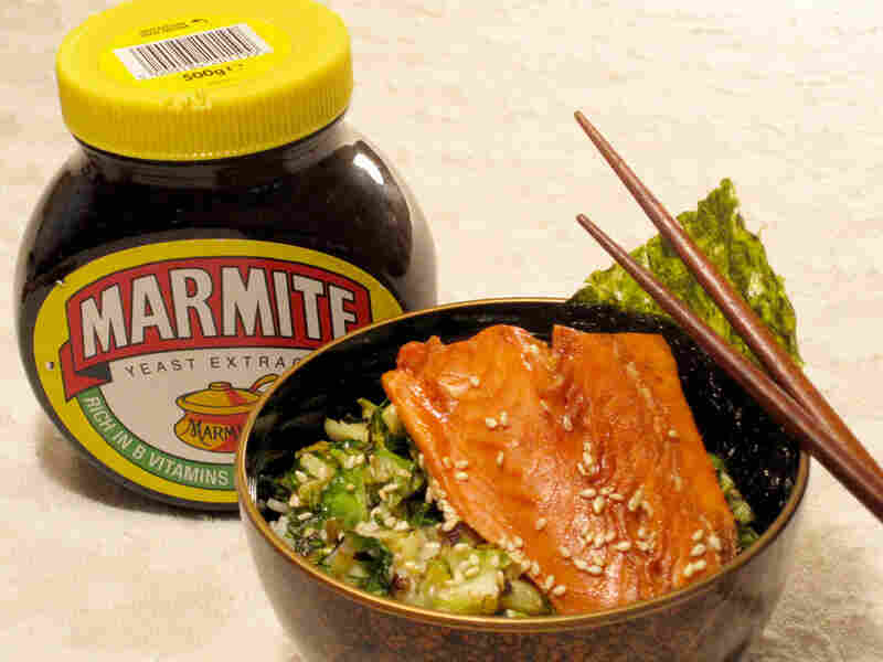 A bowl of rice topped with a salmon filet, sitting next to a jar of Marmite