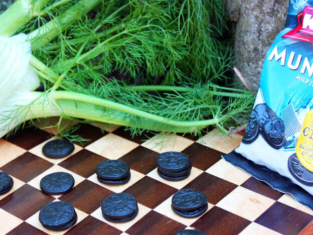 Fennel and a bag of candy sit next to a checkerboard with coin-shaped licorice candy