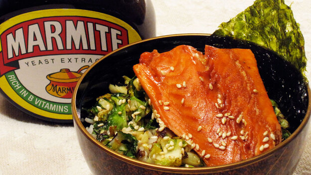 A jar of Marmite next to a bowl of rice topped with glazed salmon