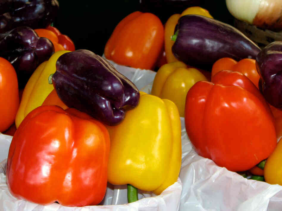 Red, purple and yellow peppers fill bags at a farmers market