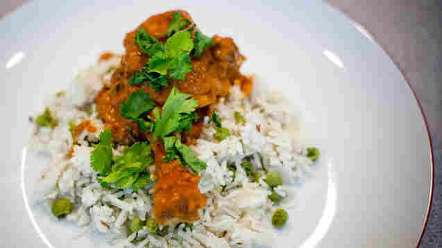 A piece of butter chicken rests on a bed of rice and peas, with a garnish of greens