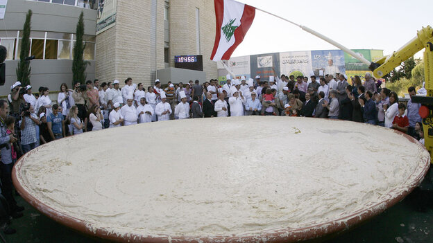 Lebanese chefs celebrate around a large plate of hummus May 8 in Beirut