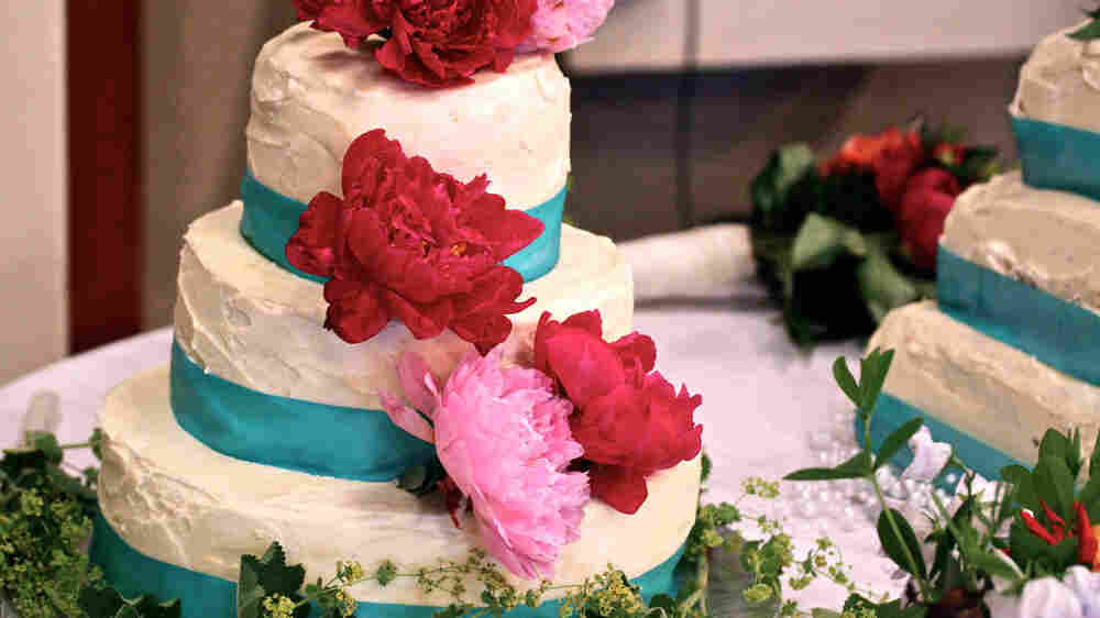 A three-tier round, white-frosted wedding cake with turquoise ribbon and red and pink flowers