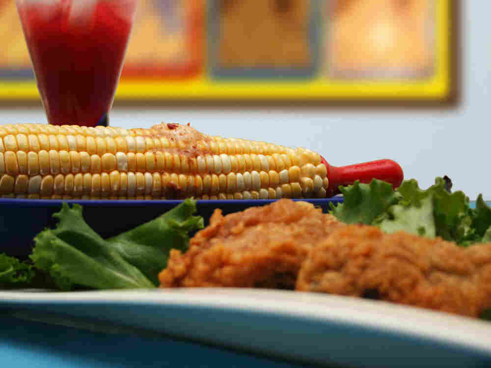A buttered ear of corn sits on a dinner plate.