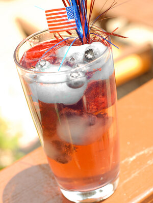 A glass holds multicolored fruit-juice ice cubes and seltzer, with an American flag decoration