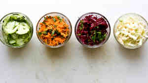 Salads (from left) in small round bowls: Cucumber, Carrot, Beet and Cole Slaw