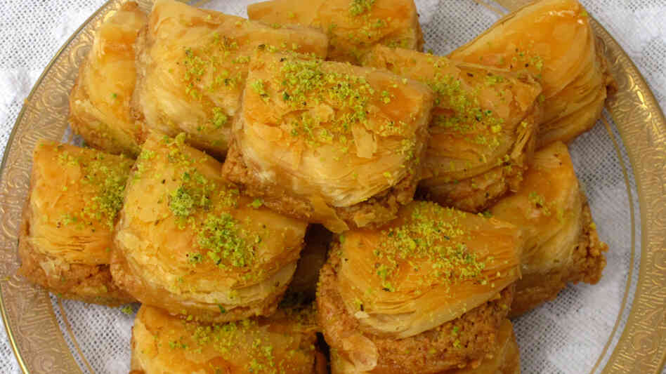 A plate full of baklava, cut into squares and dusted with ground pistachio