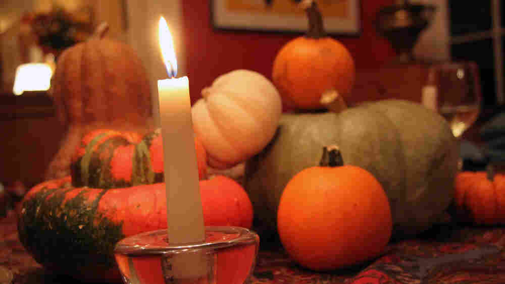 An assortment of winter squash on a candlelit dinner table