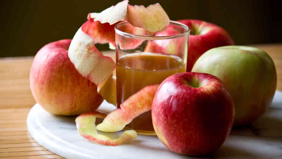 A glass of apple cider is nestled among apples of varying hues on a marble charger
