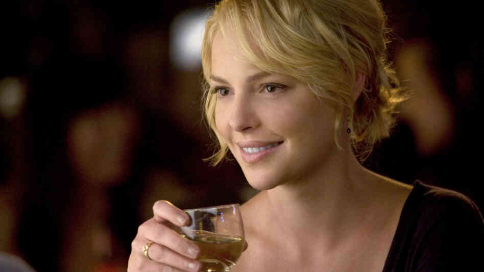 Katherine Heigl holds a glass of wine