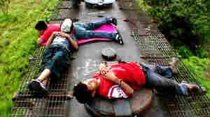W: Migrant children Fito, Jairo and Kevin ride atop a freight train
