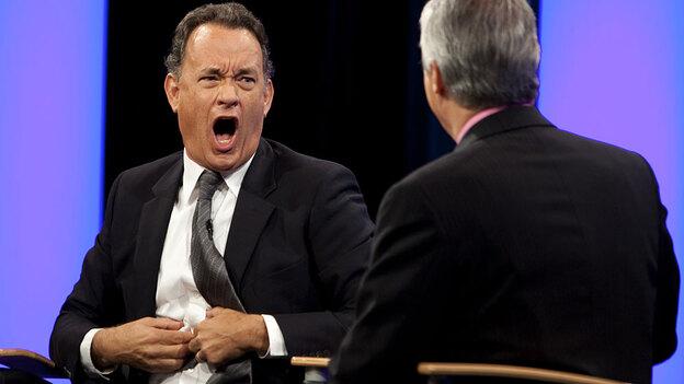 W: Tom Hanks makes a face at Scott Simon.
