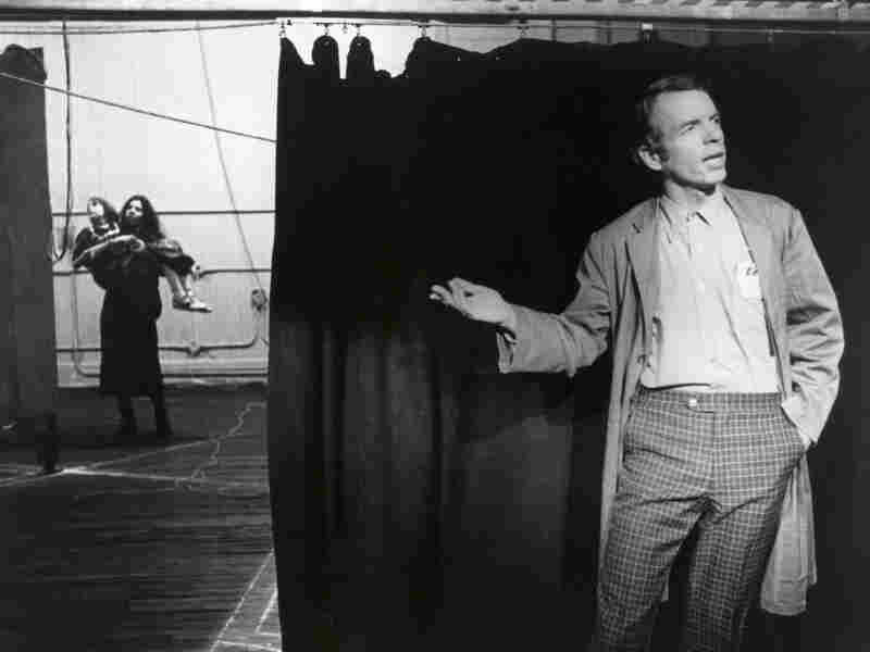 Spalding Gray by a stage curtain
