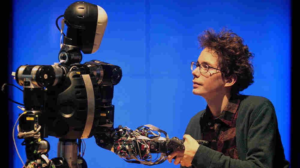 A science museum employee shakes hands with BERTI the robot at the Science Museum, in London on Febr