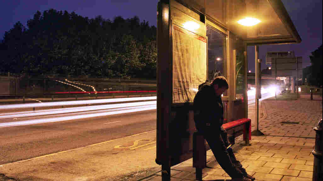 A man waits at a bus stop.